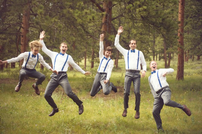 bride's men jumping with blue suspenders
