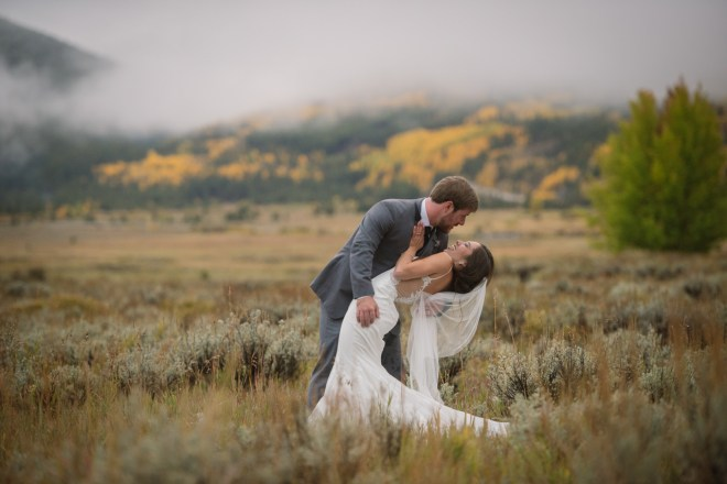 Groom and Bride dip with mountain background