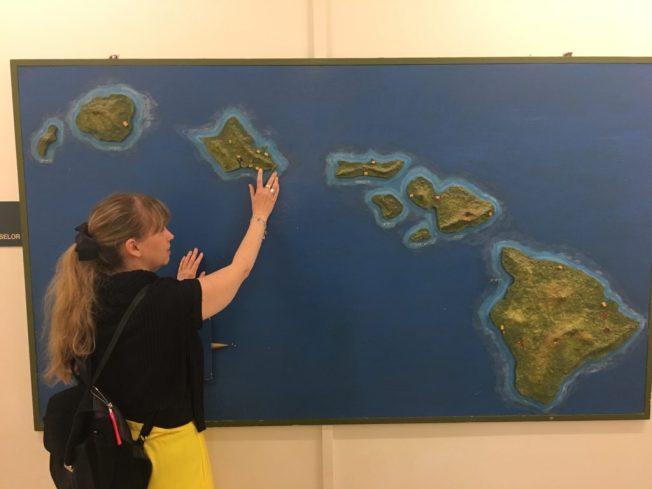 Foto på Anna när hon känner på den taktila kartan över Hawaii.
