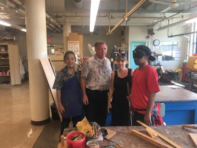 Foto när Anna besöker Division of Rehabilitation/Service for the blind. Här i verkstaden med Dean, läraren och en student som bär mörklagda glasögon.