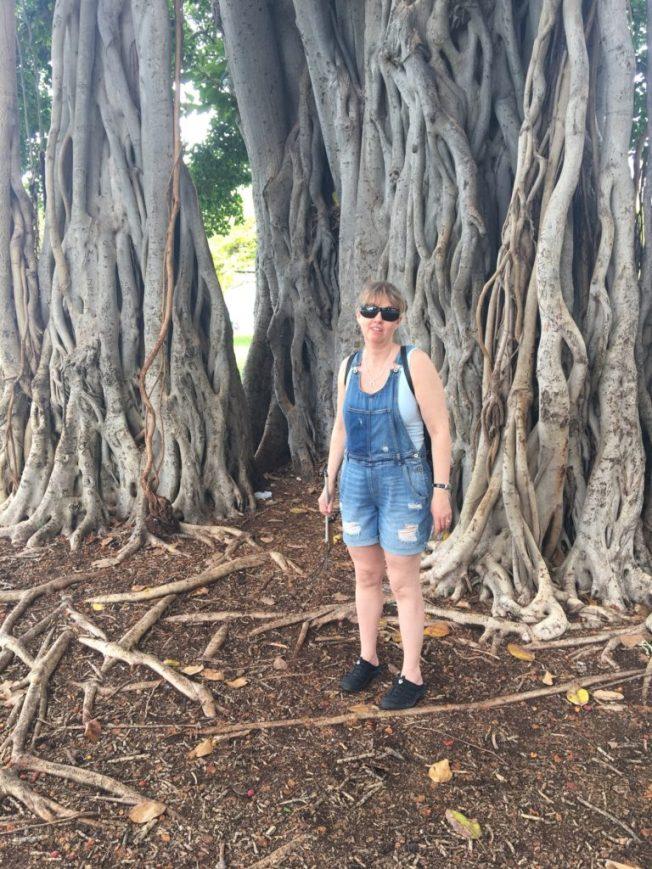 Foto på Anna i parken framför et stort träd. Grenarna slingrar sig om varandra likt ett sagoträd.