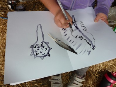 Photograph of a student drawing a feather.