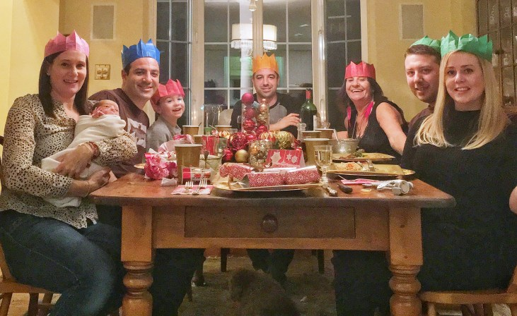 a fair skinned family sitting around a dinning room table at Christmas dinner, wearing paper crowns, the mother holds the 10 day old baby girl