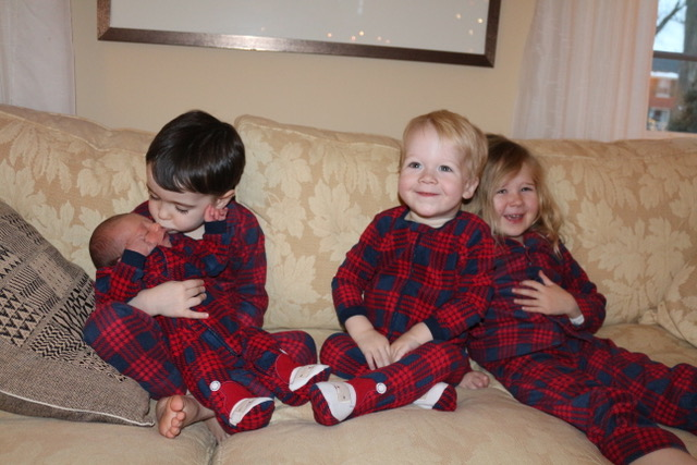four little kids sit on a couch, a 4 year old holds his 10 day old baby sister, a two year old and another 4 year old sit with them smiling