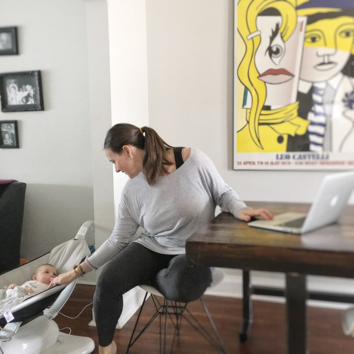 a mother sitting at a table with her lap top, leavning behind her to talk to her baby, wearing black tights (a weight loss staple) and a lose long grey shirt
