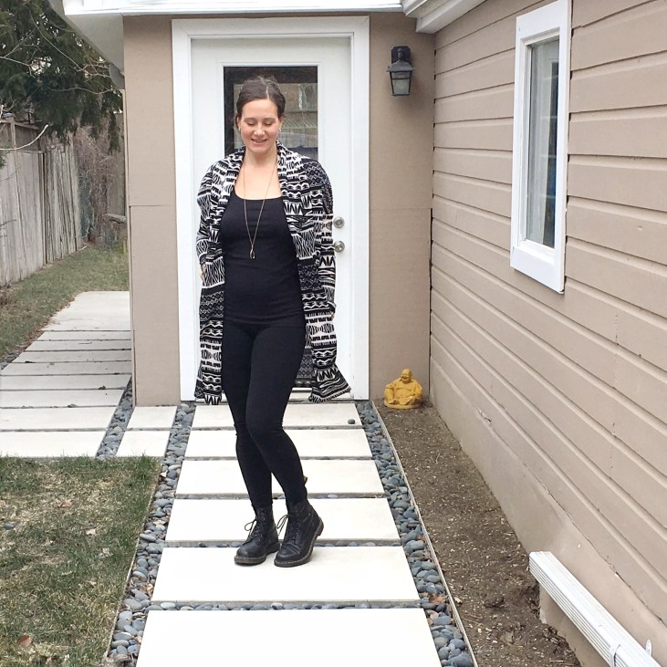 a fair skinned mother stands outside on a modern concrete path wearing black tights and a black tank top with a white and black long cardigan over top and doc martin boots