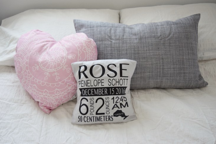 decorative pillows on the guest bed in the baby girl nursery, a pink heart pillow, a grey pillow and a pillow with baby's name, birthdate, weigh, time/place of birth listed on it