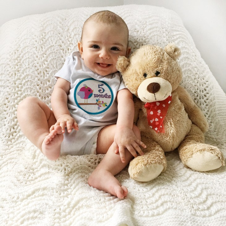 """5 month old light skinned baby girl sitting up next to a teddy bear smiling with her tongue out, wearing a shirt that says """"5 months"""""""