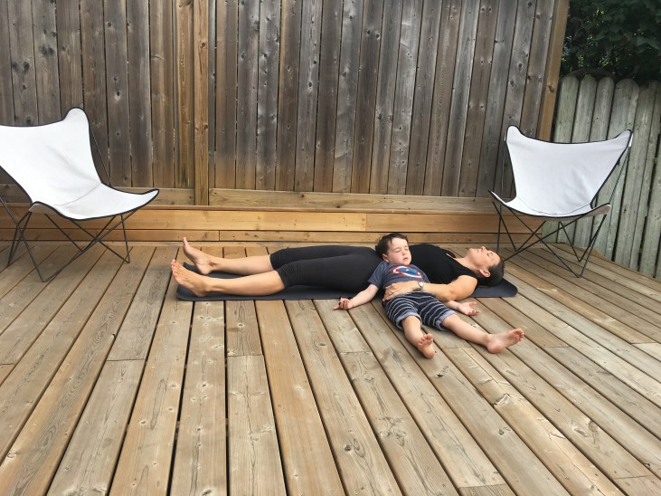 mother and son on a yoga mat doing savasana together to reduce stress