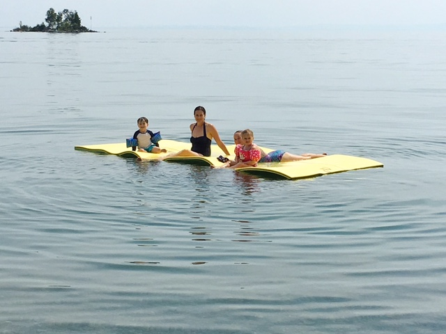 two light skinned moms sitting on a wateraft floating foam raft with a four year old girl and boy wearing water wings