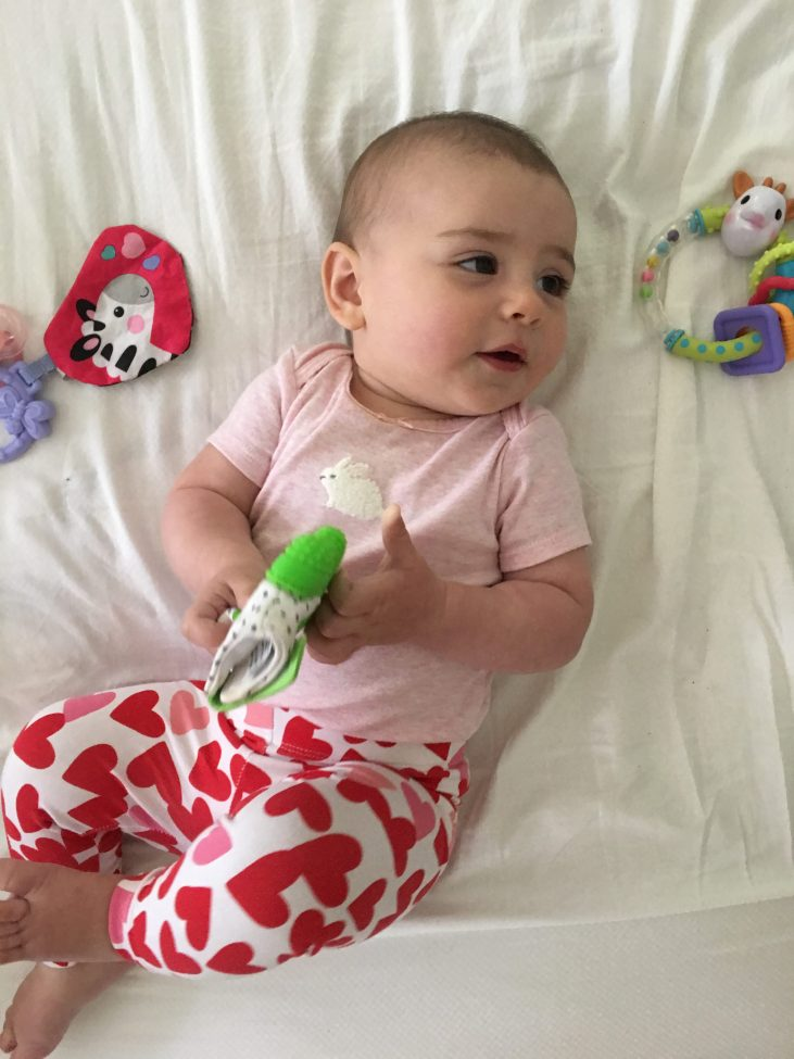 tips for teething: baby girl 8 months laying on a bed surrounded by teething toys