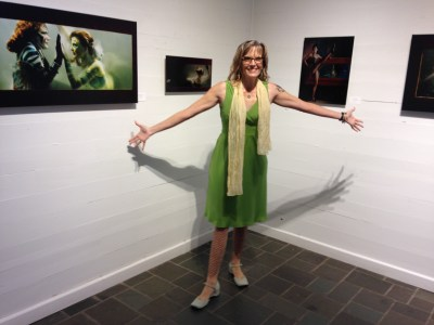 Artist Annaliese Tassano stands in front of some of the pieces at her solo artshow, The Mermaid Project Chapter One: Confinement.