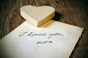a cardboard heart and and old sheet of paper with the tex I love you, mom written in it on a rustic wooden table, with a retro effect and a slight vignette added