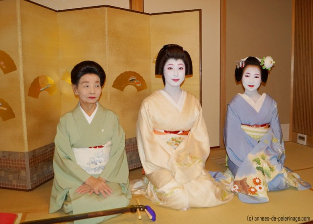 three geishas (one maiko and one geiko) sitting