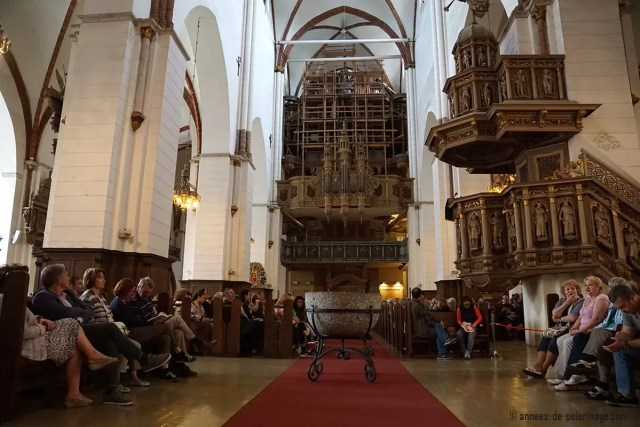 The inside of riga cathedral with the organ and people listenting to the organ concert
