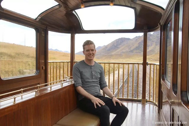 Me sitting on the luxury train by peru rail, called Andean Explorer, on the last wagon, ie the observation deck; with a standard day outfit in case you are wondering what to pack for peru