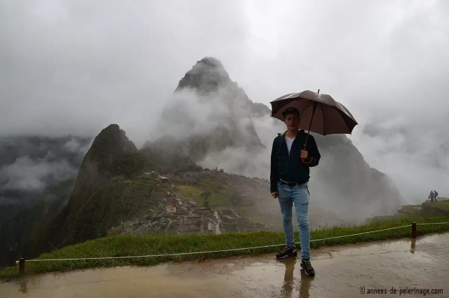 Me standing in Machu Picchu holding an umbrella with heavy rains making the paths very muddy
