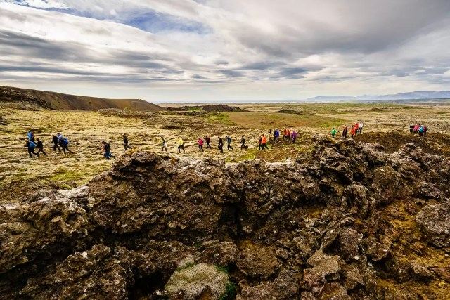 A group of wanders walking through a valley in Iceland - all wearing hiking boots and some with walking sticks
