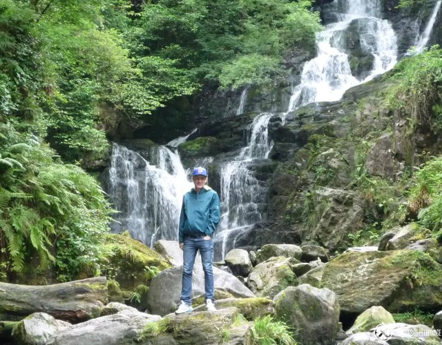 Me standing in front of a waterfall in Ireland. As you can see, I packed a rain coat, trainers and a hat. I think those are essential