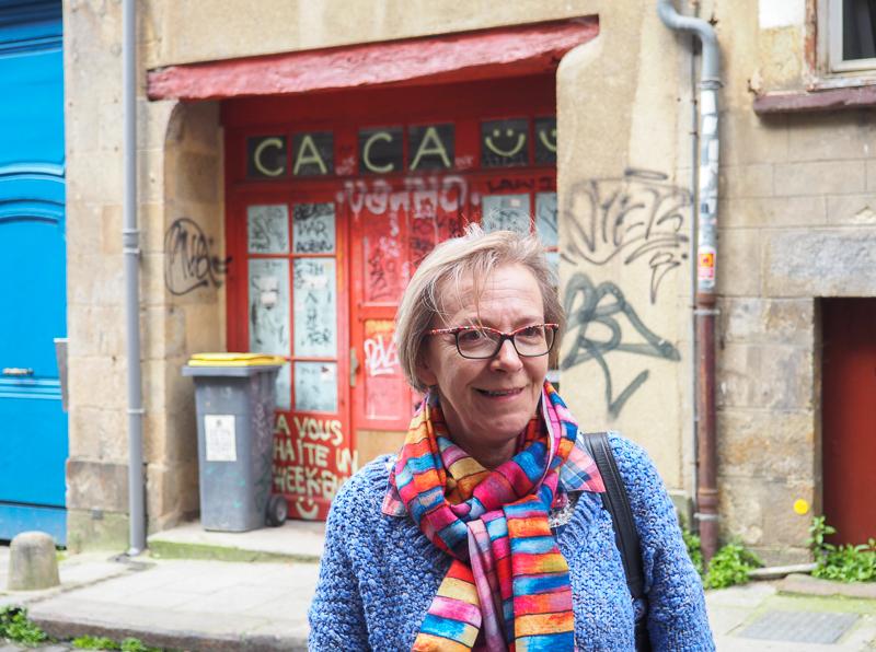 Guide de notre visite guidée de Street Art devant une signature de l'artiste CACA.