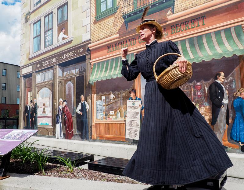 Murales historiques au centre-ville de Sherbrooke avec comédienne qui la présente.