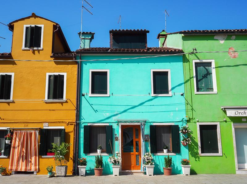 Maisons jaune, turquoise et verte sur l'île de Burano dans la lagune de Venise