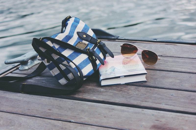 sacoche, livre et lunettes de soleil sur un quai