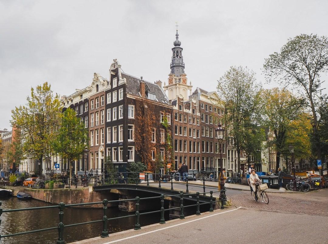 Femme à vélo dans un quartier d'Amsterdam, devant des canaux et des maisons typiques.