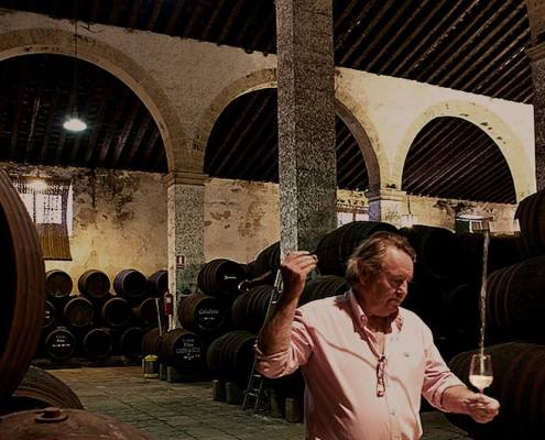 man pouring sherry from the barrel