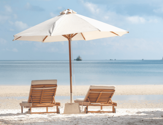 Two Brown Wooden Armchairs Beside Umbrella Near Seashore