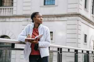 dreamy black student with agenda against urban building