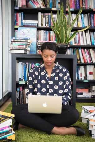 woman sits on floor facing gold macbook