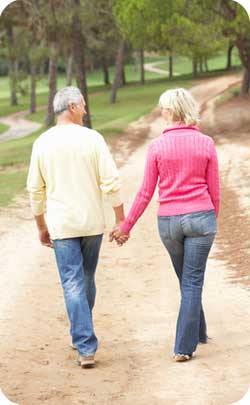 older married couple walking hand in hand through forest