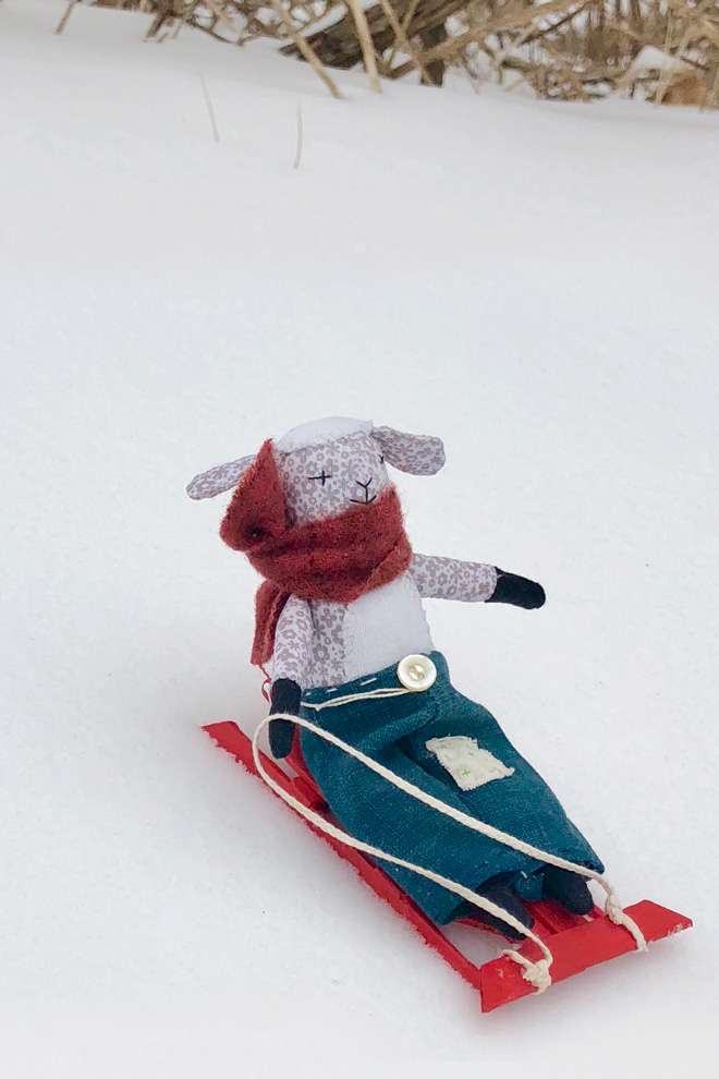 lamb doll on a popsicle stick sled in the snow