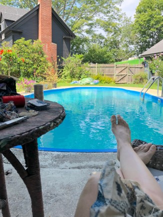 a work table and feet on a lounge by a bright pool