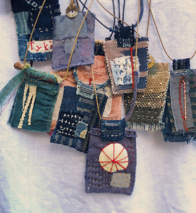 amulets stitched from antique textiles worn with a white smock