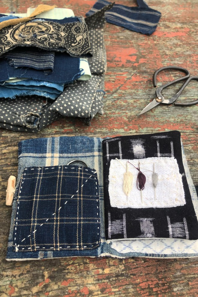 cloth book with pockets and pre-threaded sewing needles