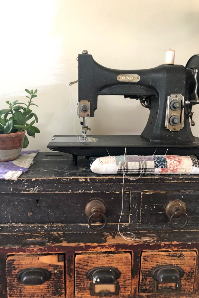 long pin cushion on tool chest with antique sewing machine