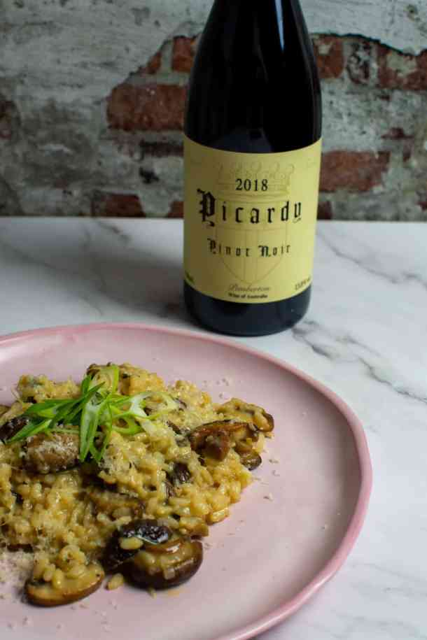 wild mushroom risotto on pink plate with a btl of picardy pinot noir