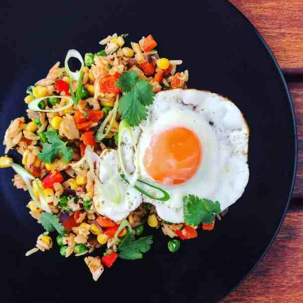 Fried rice, fried egg on a black plate