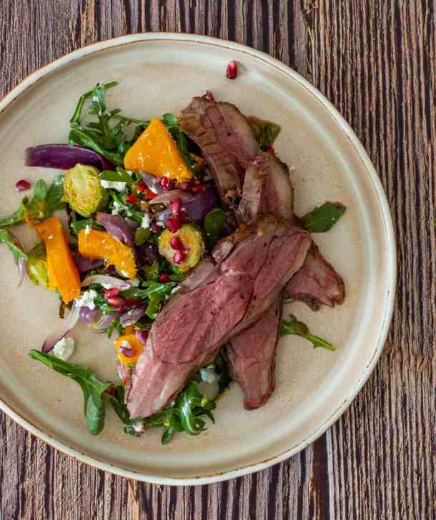 cooked lamb, veg salad on a plate