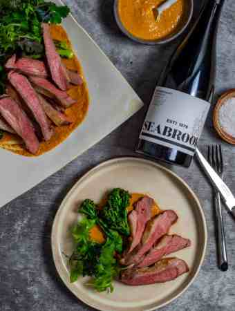 Seabrook wine shiraz, BBQ lamb, romesco sauce & charred broccolini on a table