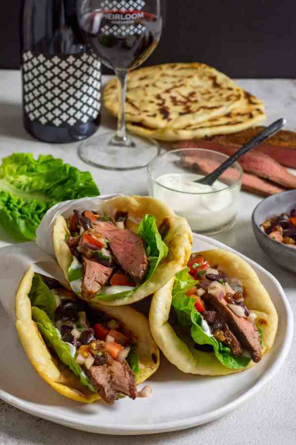 red wine, morrocan steak pitas, yoghurt & steak on a table