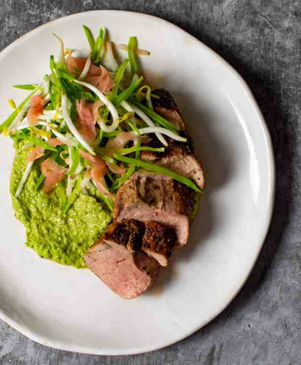 pork loin, avocado & pea hummus & beansprout salad on a plate