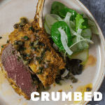 crumbed veal cutlet sliced in half with lemon caper sauce and salad