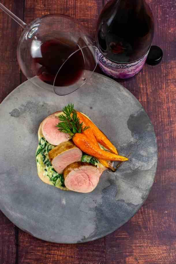 pork tenderloin, creamed spianch & carrots on a made of australia plate with a btl of mazzini pinot noir