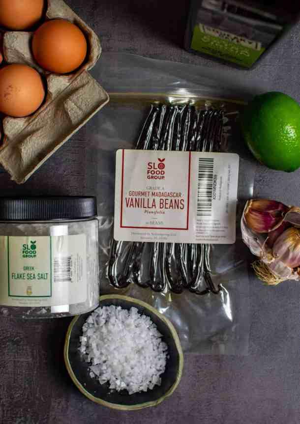 slofoodgrp vanilla, eggs, salt, lime & garlic on counter top