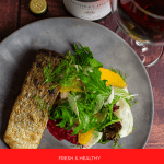 grilled salmon, beetroot hummus & fennel salad on a made of australia plate and a moores hill pinot noir