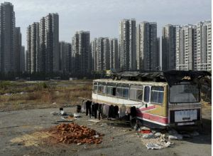 Clothes are seen hanging outside a bus which has been converted into a dwelling for Lu Changshan and his wife near newly-constructed residential buildings in Hefei, Anhui province in China on November 12, 2012 (Jianan Lu/Courtesy Reuters).