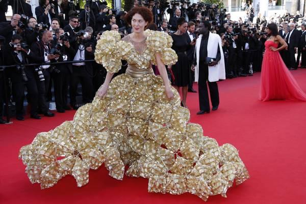 Una modella sul red carpet indossa un abito fatto di scatole di biscotti